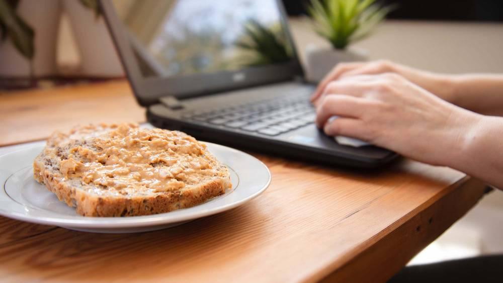 Peanut butter on bread beside a woman working on laptop